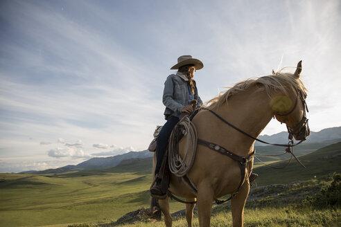 Female rancher on horseback looking away remote field - HEROF28828