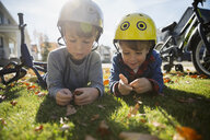 Brothers laying in grass playing with autumn leaves - HEROF28906