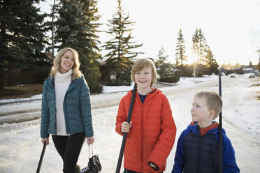 Smiling mother and sons walking with ice hockey sticks and ice skates on snowy road - HEROF28960