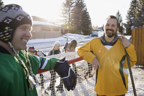 Smiling men playing ice hockey in sunny, snowy driveway - HEROF28966