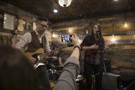 Woman in audience taking selfie behind musicians performing on garage stage - HEROF28978