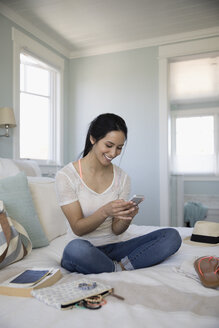 Smiling woman packing for vacation, texting on bed - HEROF29020