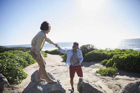 Young couple holding hands climbing rocks at sunny beach - HEROF29077