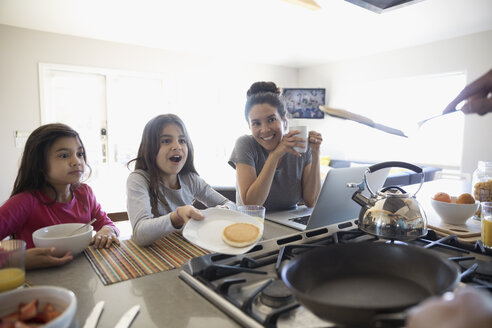 Smiling daughters and mother watching father flipping pancake in kitchen - HEROF29116