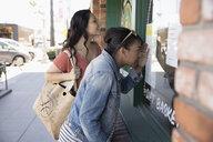 Women friends window shopping at storefront - HEROF29131