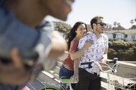 Smiling couple with bicycle on sunny bridge - HEROF29140