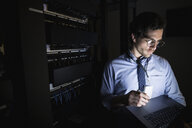 Technician using laptop in dark server room - HEROF29170
