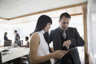 Businessman and businesswoman with digital tablet talking in conference room - HEROF29248