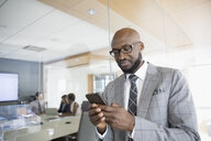 Businessman texting with cell phone outside conference room meeting - HEROF29251