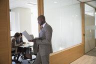 Businessman using laptop in conference room doorway - HEROF29257