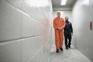 Bailiff walking prisoner in orange jumpsuit down corridor in jail - HEROF29320