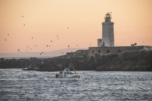 Spain, Andalusia, Tarifa, fishing boat in front of lighthouse - KB00594