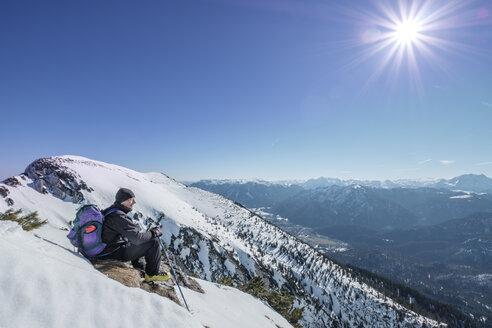 Germany, Bavaria, Gamsknogel, Weissbach, Chiemgau, senior man sitting in winter landscape - HAMF00568