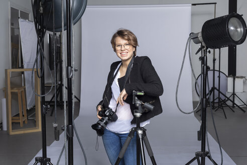 Portrait of smiling young photographer with equipment at photographic studio - VGF00238