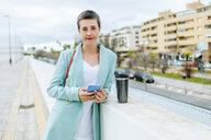 Woman dressed in jacket suit with smartphone and thermo mug - KIJF02419