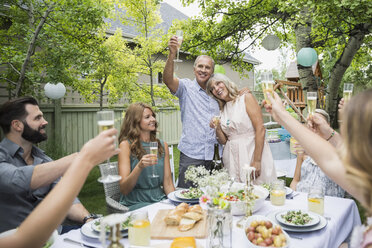 Family toasting champagne flutes at garden party - HEROF29354