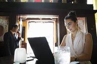 Businesswoman working at laptop in pub - HEROF29375