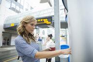 Businesswoman checking schedule at train station - HEROF29381