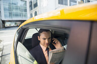 Businessman reading newspaper talking on cell phone taxi - HEROF29384