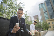 Businessman texting with cell phone in city - HEROF29405