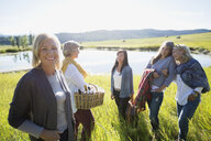 Portrait smiling woman with friends sunny grass lake - HEROF29465