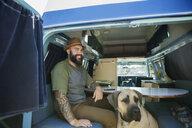 Smiling bearded man with dog in camper van - HEROF29483