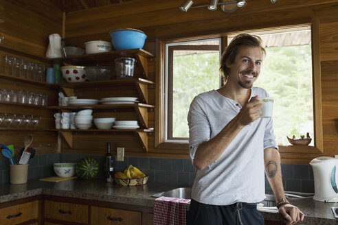 Portrait smiling man drinking coffee in cabin kitchen - HEROF29495
