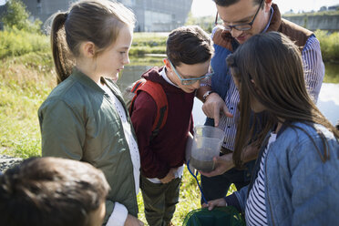 Science teacher and students examining water field trip - HEROF29534