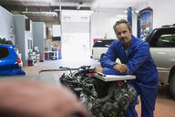 Portrait confident mechanic at engine auto repair shop - HEROF29579