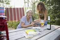 Mother and daughter using digital tablet campsite table - HEROF29591