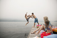 Playful father throwing son into lake from dock - HEROF29636