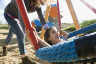 Mother pushing daughter on swing at sunny playground - HEROF29645