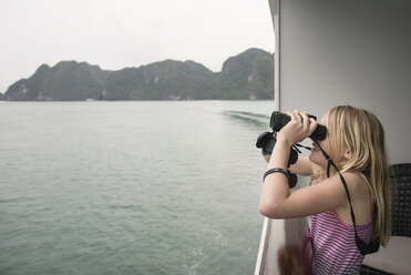 Side view of girl looking through binoculars while standing in boat on sea against sky - CAVF63158