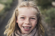 Close-up portrait of happy girl with blond hair standing in forest - CAVF63185