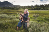 Portrait of father with cute daughters standing on grassy field against sky in forest - CAVF63212