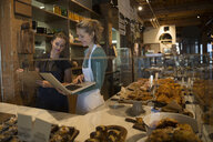 Bakery owner and worker with laptop and clipboard - HEROF29704