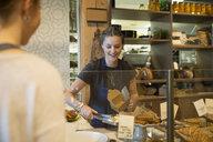 Bakery worker serving customer pastries behind the counter - HEROF29707