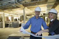 Architect and engineer reviewing blueprints office construction site - HEROF29770