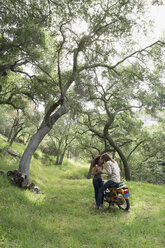 Affectionate young couple on motorcycle in woods - HEROF29776