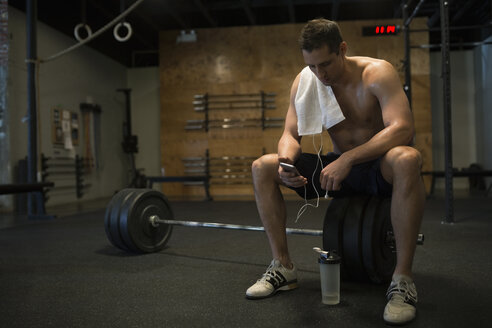 Bare chested man resting checking cell phone gym - HEROF29788