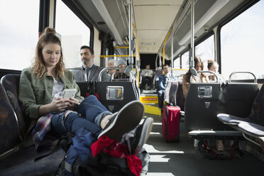 Young woman texting with cell phone on bus - HEROF29831