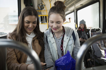 Teenage girls texting with cell phone on bus - HEROF29837