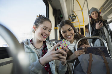 Teenage girls texting with cell phone on bus - HEROF29843