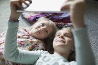 Smiling sisters taking selfie with digital tablet on floor - HEROF29864