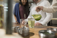 Tea shop owner pouring green tea for customers - HEROF29873
