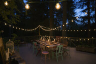 String lights and candles on balcony and dining table at night - HEROF29900