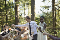 Smiling bride and groom toasting friends on balcony at wedding reception - HEROF29933