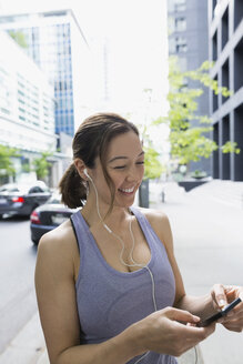 Smiling runner with headphones and mp3 player on city street - HEROF29951