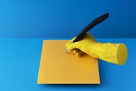 Quill pen held in hand and writing on orange paper over blue background - DRBF00142