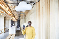 Mature businessman holding cell phone attached to cloud balloon - FMKF05446